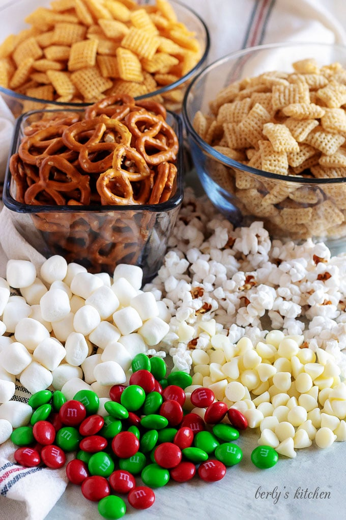 Pretzels, marshmallows, corn Chex, rice Chex, M&Ms, popcorn, and white chocolate chips used for Christmas Chex Mix.
