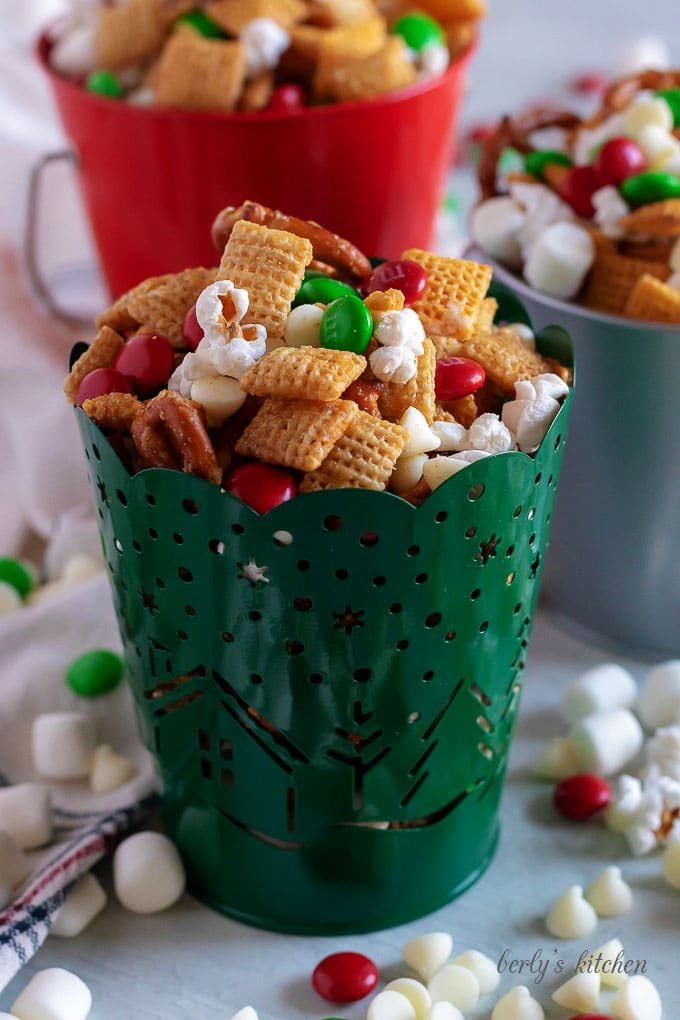 Christmas Chex Mix in red, green, and silver tins.