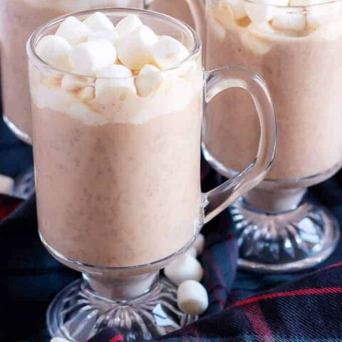 4 mugs of Instant Pot hot cocoa topped with marshmallows.