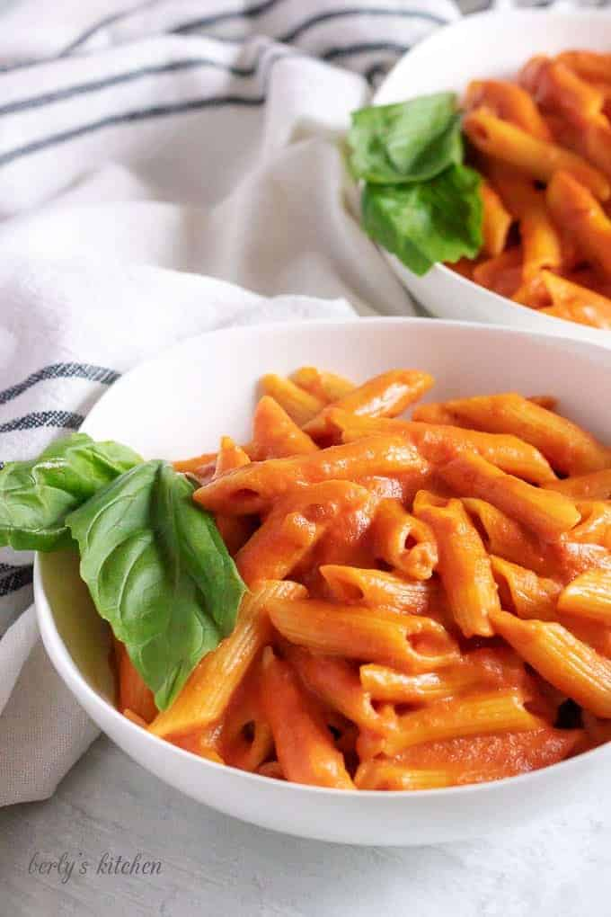 Two white bowls filled with penne with vodka sauce and fresh basil.