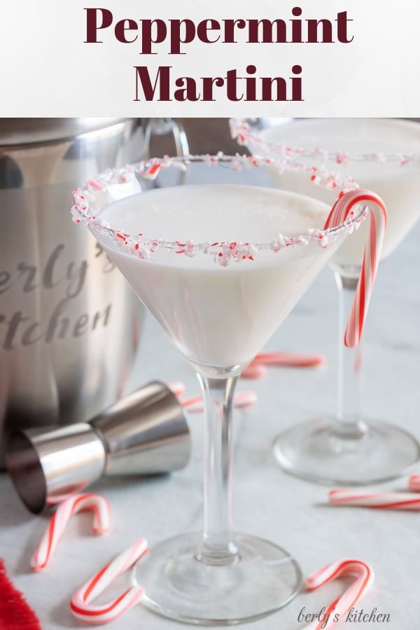Two finished peppermint martinis with a candy cane garnish, and rimmed with crushed candy canes.