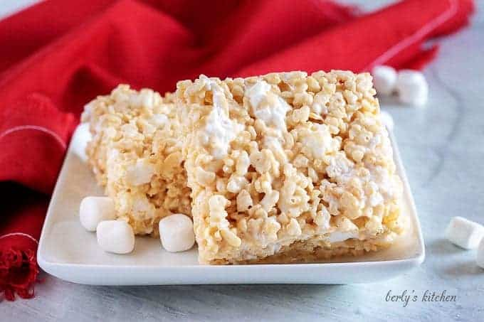Two perfect rice krispie treats on a square plate next to marshmallows and a red napkin.