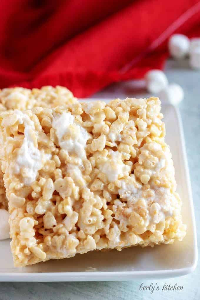 Two large rice krispie treats on a white plate next to a red napkin.
