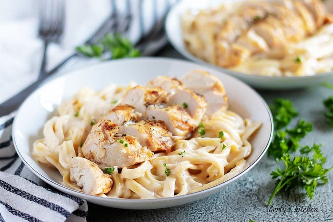 A bowl with fettuccine covered in Alfredo sauce and topped with chicken.