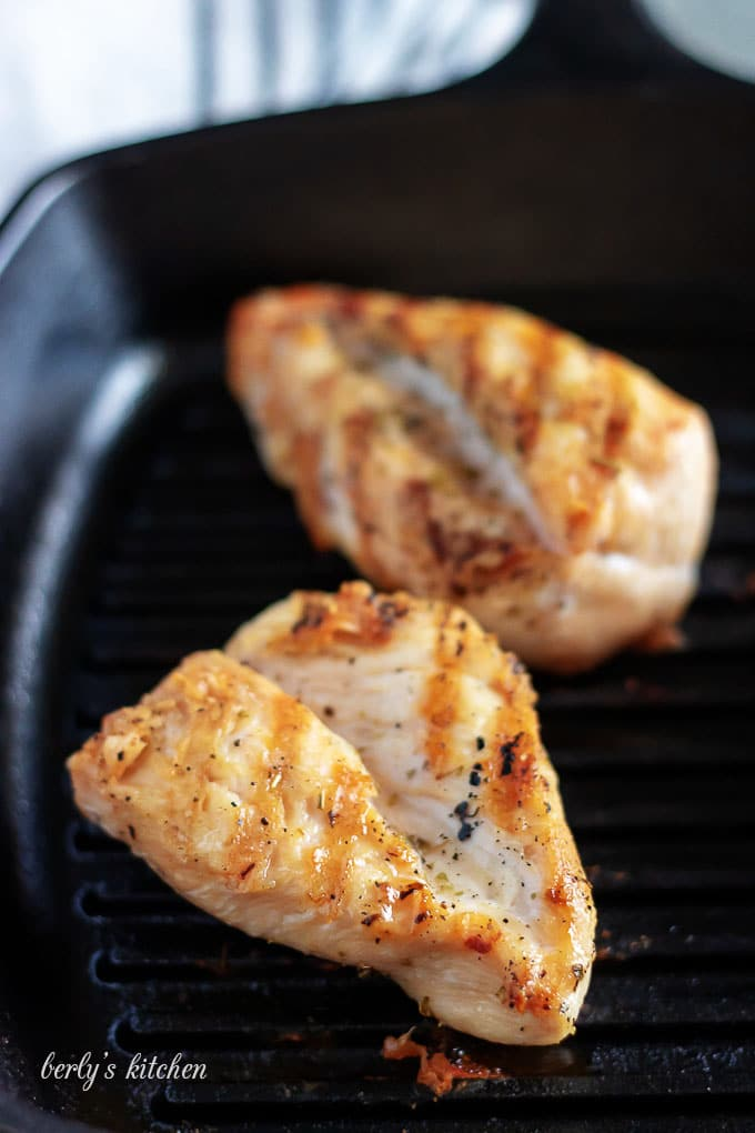 Two pieces of chicken breast being cooked on a hot griddle.