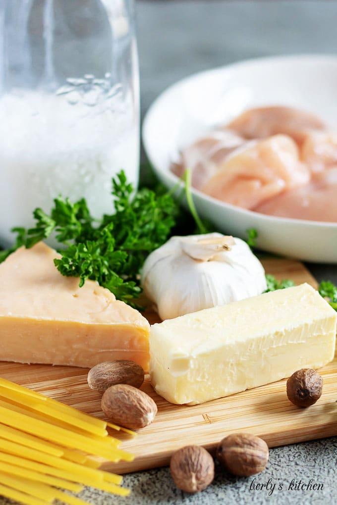 The chicken alfredo ingredients like fresh Parmesan cheese, chicken, garlic, and nutmeg.