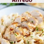 A photo of the chicken alfredo, in a bowl, garnished with parsley.