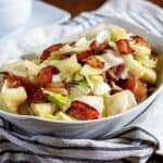 A serving dish with fried cabbage topped with crispy bacon.