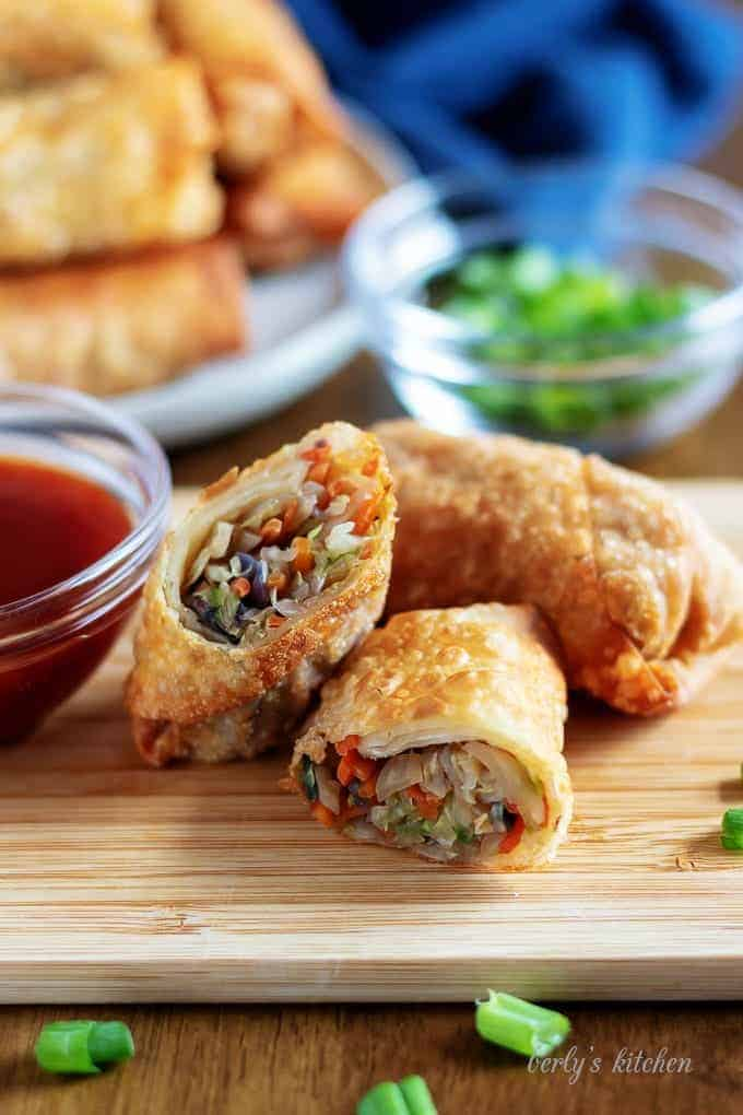 A large photo of an egg roll cut in half, with sauce.