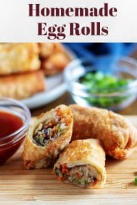 Large photo of the egg rolls, one cut in half, and served with sweet and sour sauce.