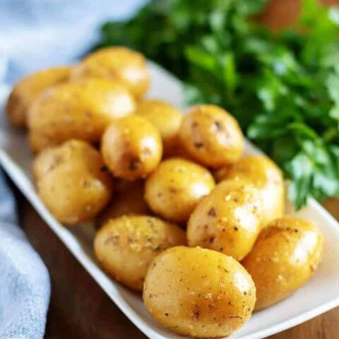 The finished baby potatoes, with fresh herbs, on a rectangular plate.