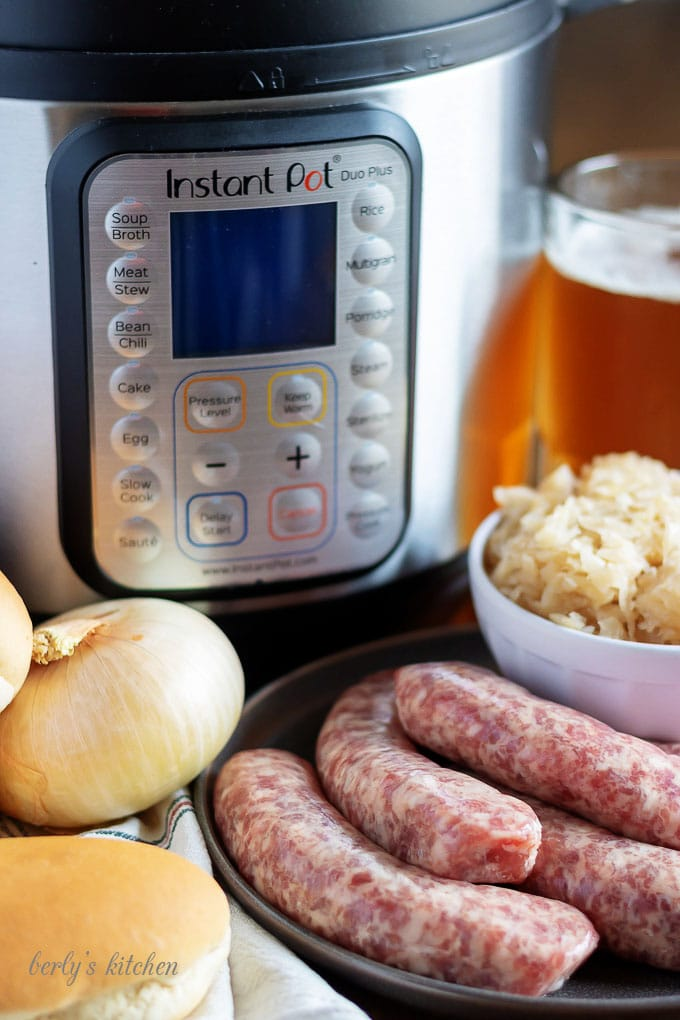 All the beer brats ingredients like beer, raw brats, and fresh onion,