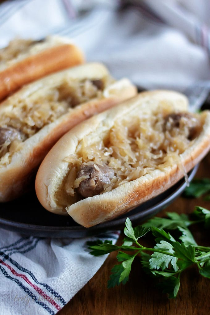 Beer brats, in buns, garnished with extra sauerkraut and sauted onions.