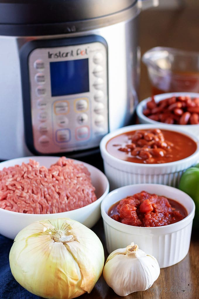 Instant pot chili recipe ingredients like beef, tomatoes, onions, and beans.