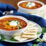 Two bowls of chili topped with cheese, green onions, and sour cream.