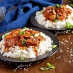 Two plates of honey garlic chicken served over white rice.