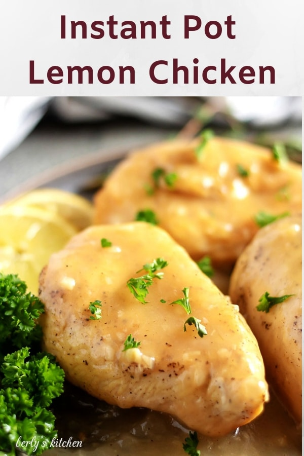 Lemon chicken breasts, garnished with lemon slices and parsley, topped with sauce.