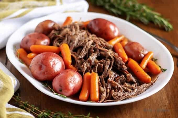The finished Instant pot pot roast surrounded by cooked carrots and potatoes.