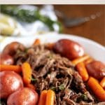 The pot roast on a platter surrounded by carrots and potatoes.