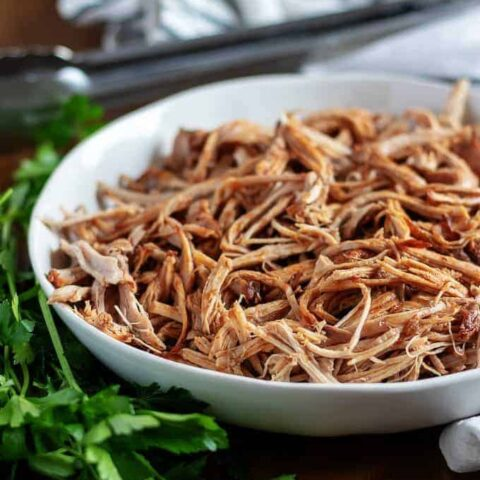 The pulled pork, ready to be served with metal tongs.
