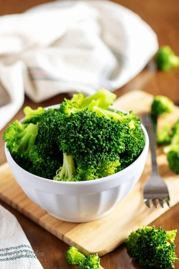 A picture of the steamed broccoli in a bowl on a cutting board.
