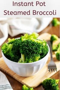 The finished steamed broccoli in a white bowl with a fork.