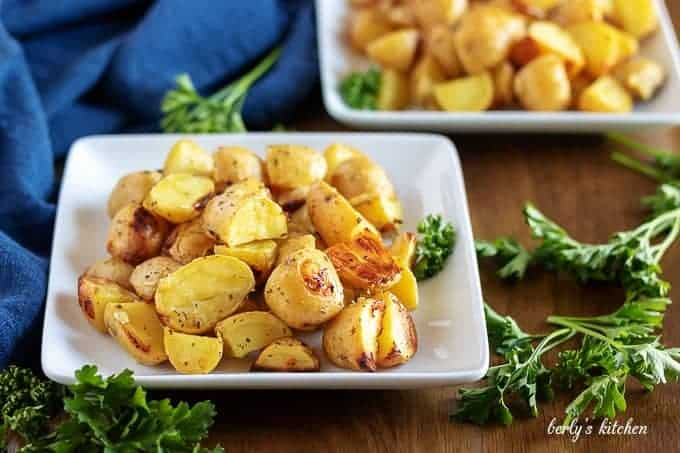The ranch potatoes, garnished with parsley, sitting in a square dish.
