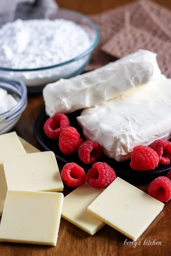 The dip ingredients like sugar, cream cheese, fresh raspberries, and white chocolate.