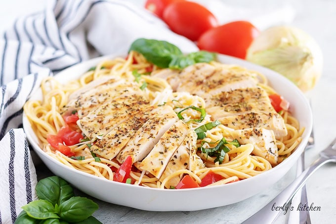 A large pasta bowl filled with the buschetta chicken pasta.