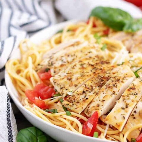 The bruschetta pasta has been topped with chicken and fresh basil.
