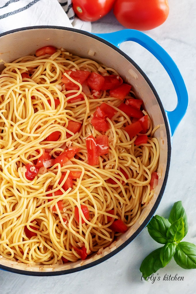 Top-down view of the pasta noodles, tossed with tomatoes and oil.