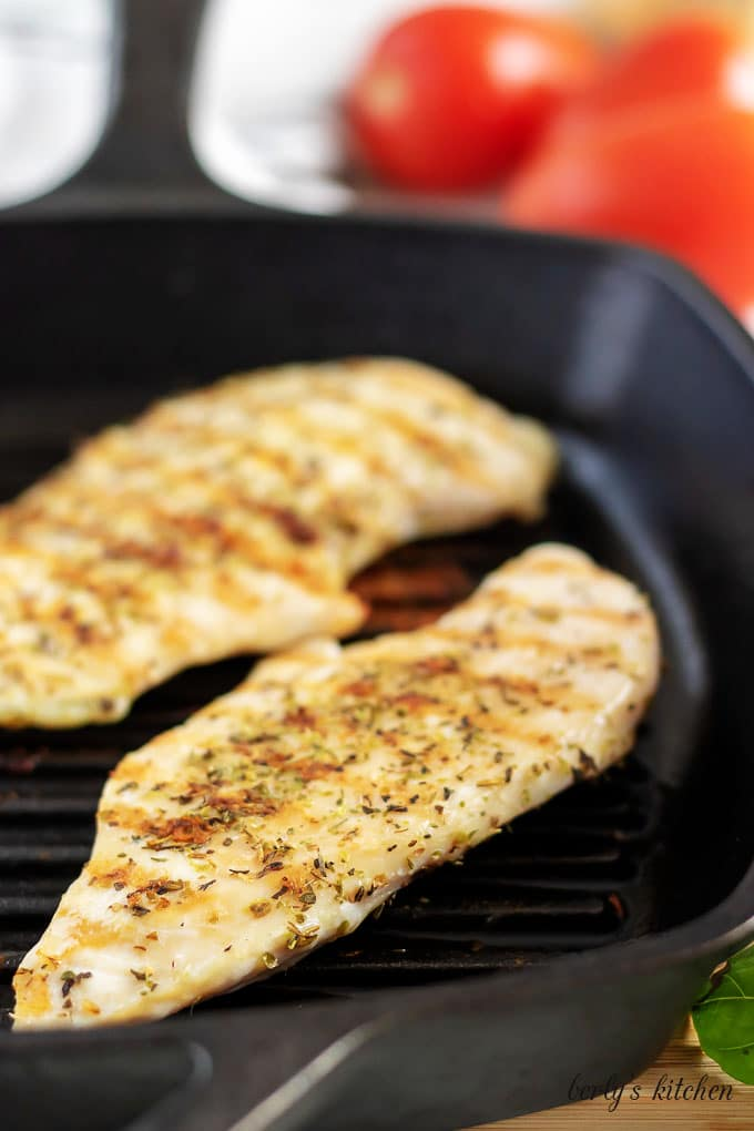 Two seasoned chicken breasts cooking in a black griddle pan.