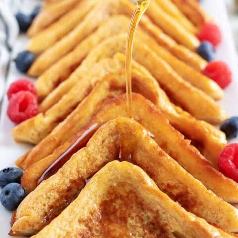 Cinnamon French Toast slices lined on a white dish with syrup.