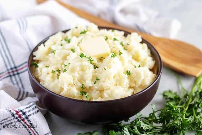 Garlic mashed potatoes in a brown bowl, topped with unsalted butter.