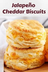 Two stacked cheddar biscuits, accented with a napkin, layered with cheddar cheese.
