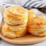 Four golden brown jalapeno cheddar biscuits stacked, in twos, on a plate.