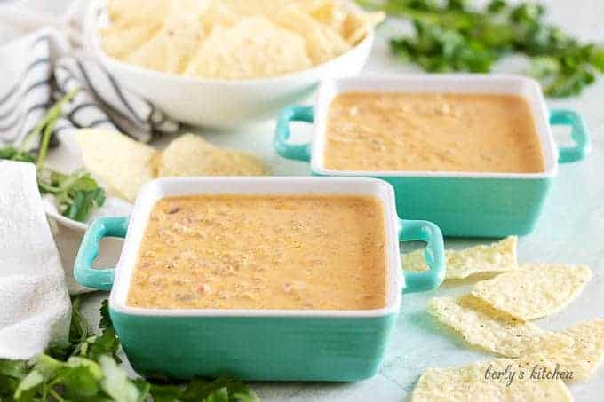 Two square bowls of seasoned beef queso dip with tortilla chips.