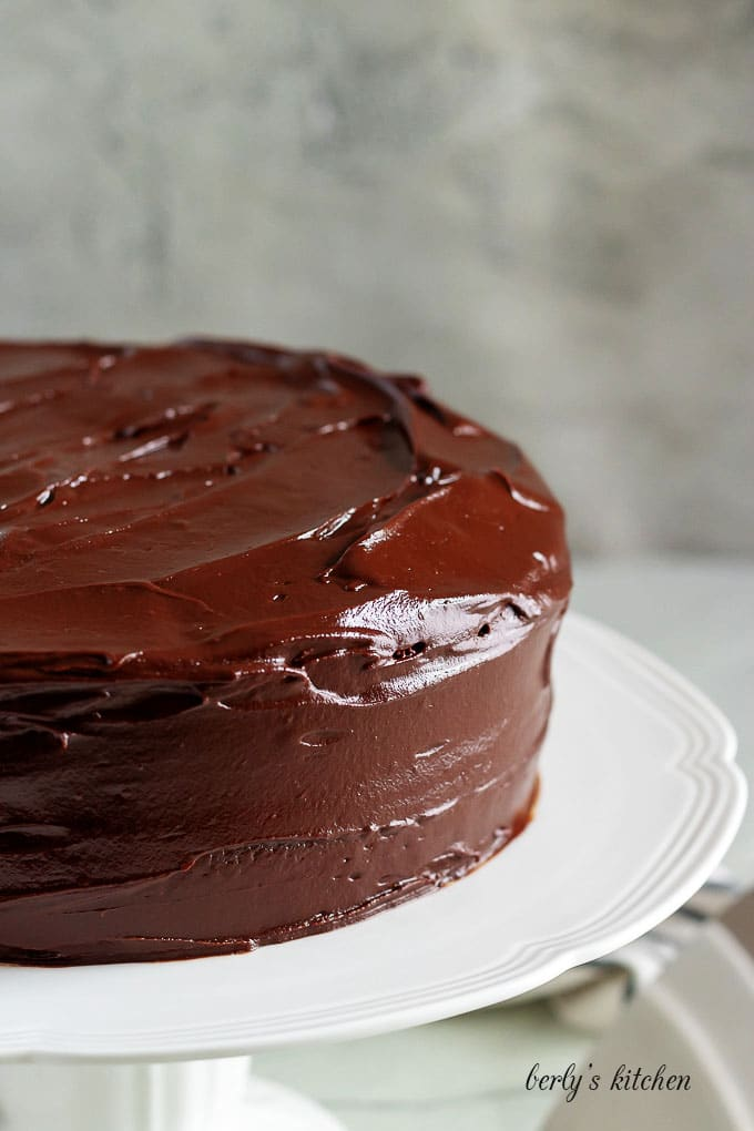 The cake has been placed on a stand and covered in ganache.