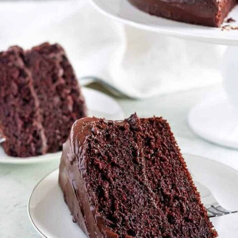 Two slices of the chocolate cake on small white plates.