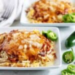 Two servings of shredded hash browns, topped with chili, cheese, and onions.