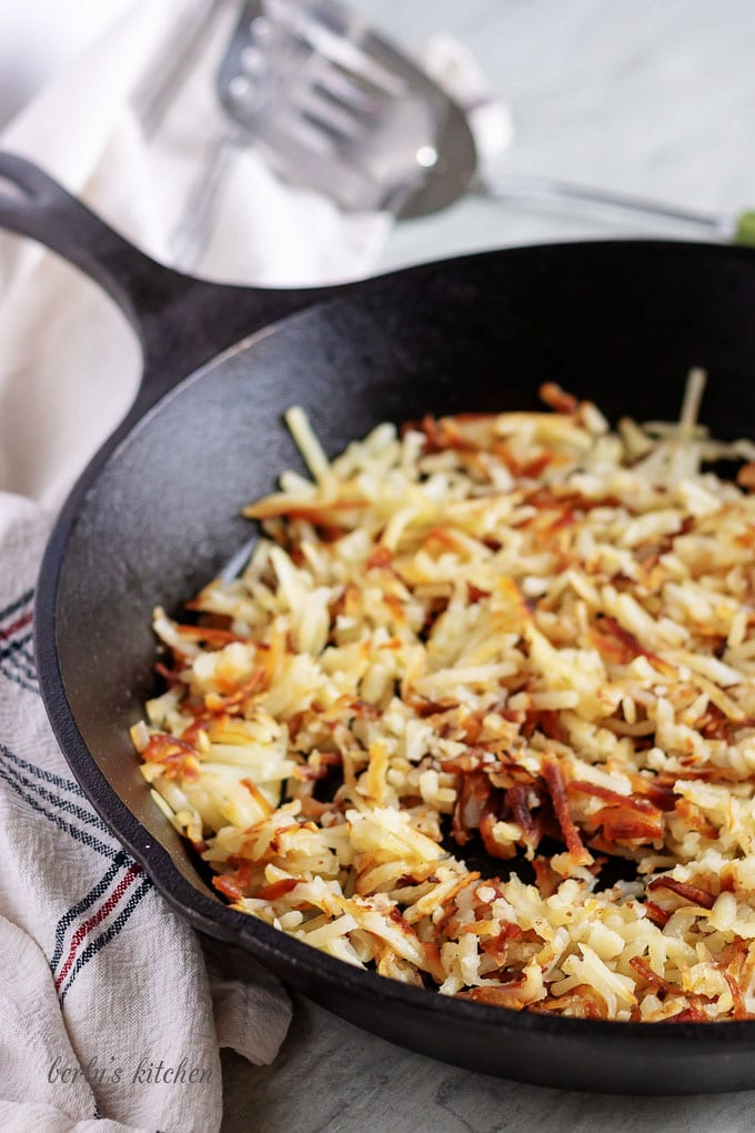 The photo shows crispy hash browns cooked in a cast iron skillet.