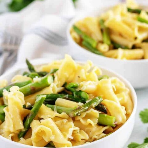 A large photo of the asparagus pasta served in white bowls.
