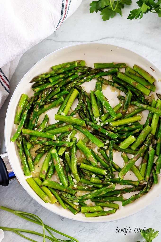 An aerial view of the asparagus and garlic sauteed in a pan.