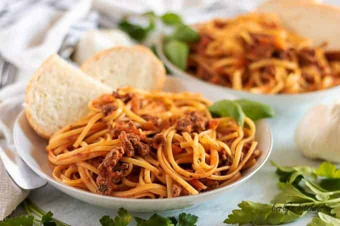 Two pasta bowls filled with beef bolognese and linguine, topped with bread.