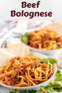 Two pasta plates loaded with beef bolognese tossed with linguine pasta.