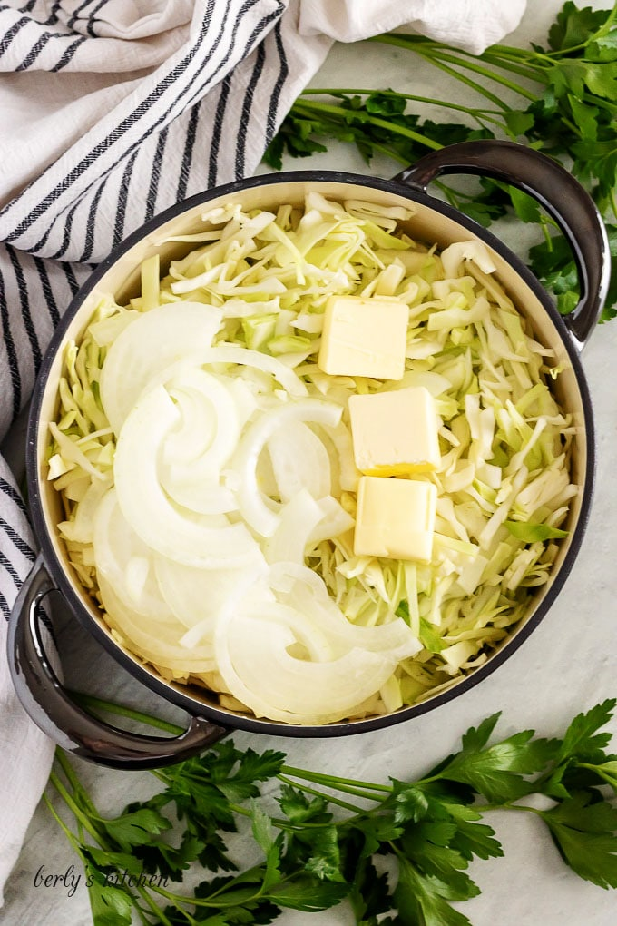 Shredded cabbage, onions, and butter, in a pan for frying.