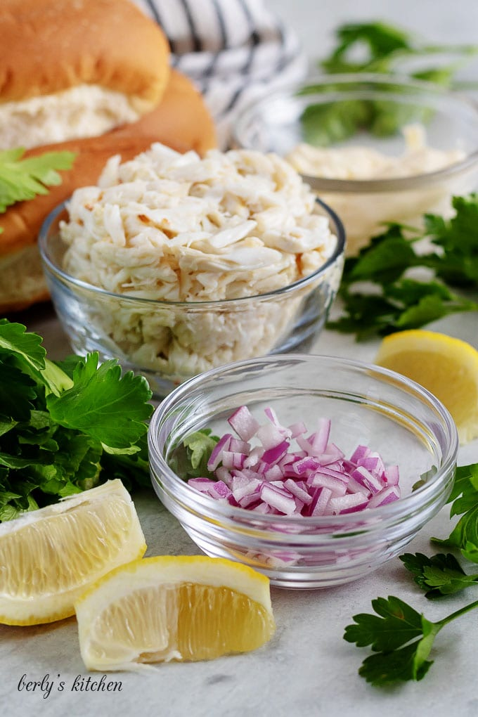 The crab roll recipe ingredients like red onions, crab meat, and buns.