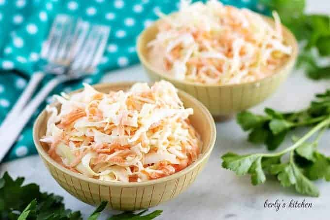 Two bowls of cream coleslaw with forks and a polka dot towel.