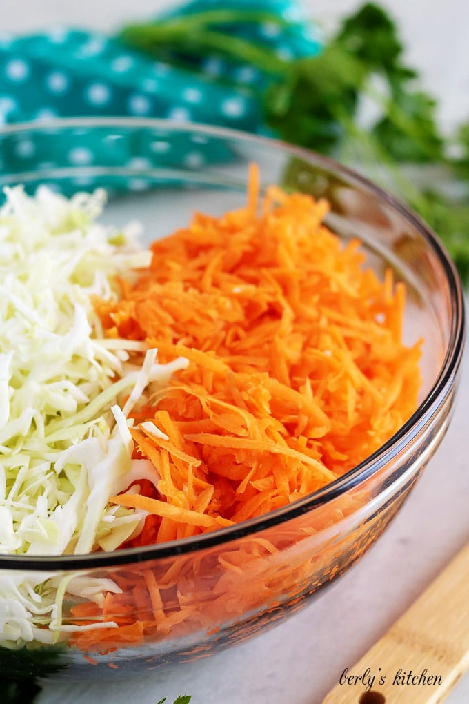 A large mixing bowl filled with shredded cabbage and carrots.