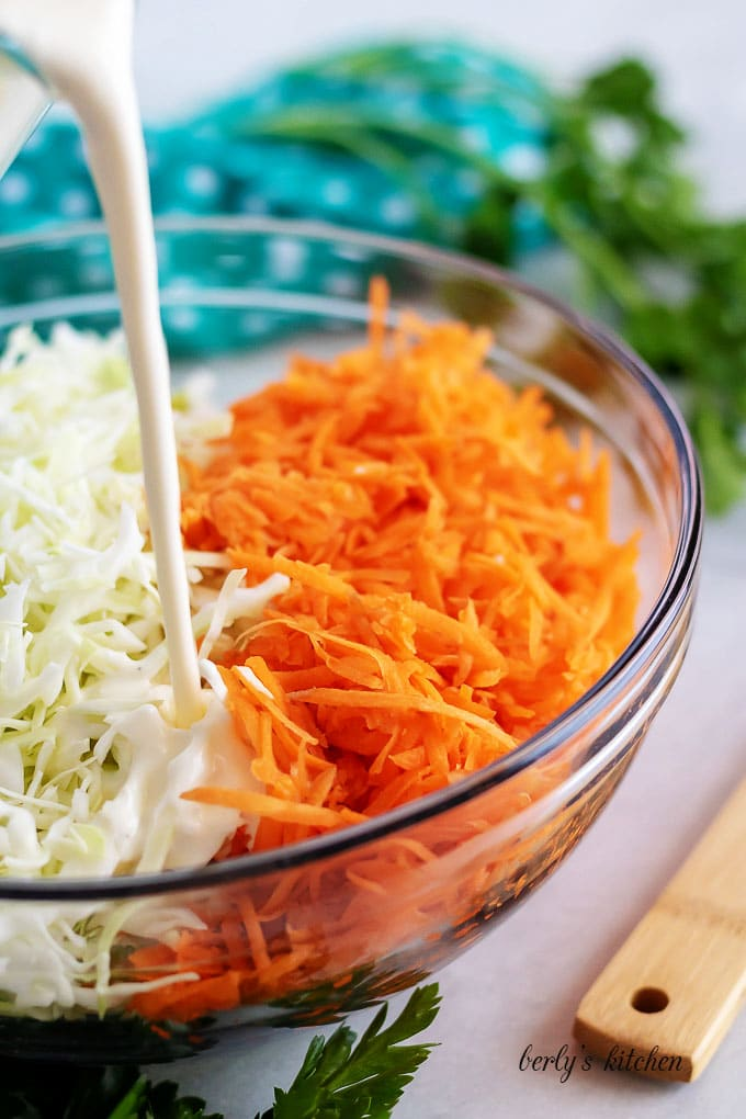 The coleslaw dressing being poured over the cabbage and carrots.